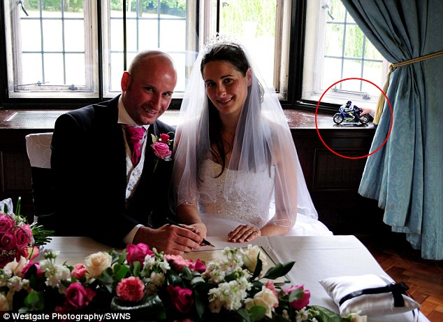 This snap of the couple signing the marriage register appears to feature a ghostly hand clutching a toy motorbike - but it