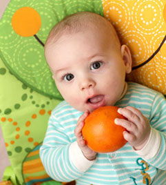 The baby boy posing with a orange at home